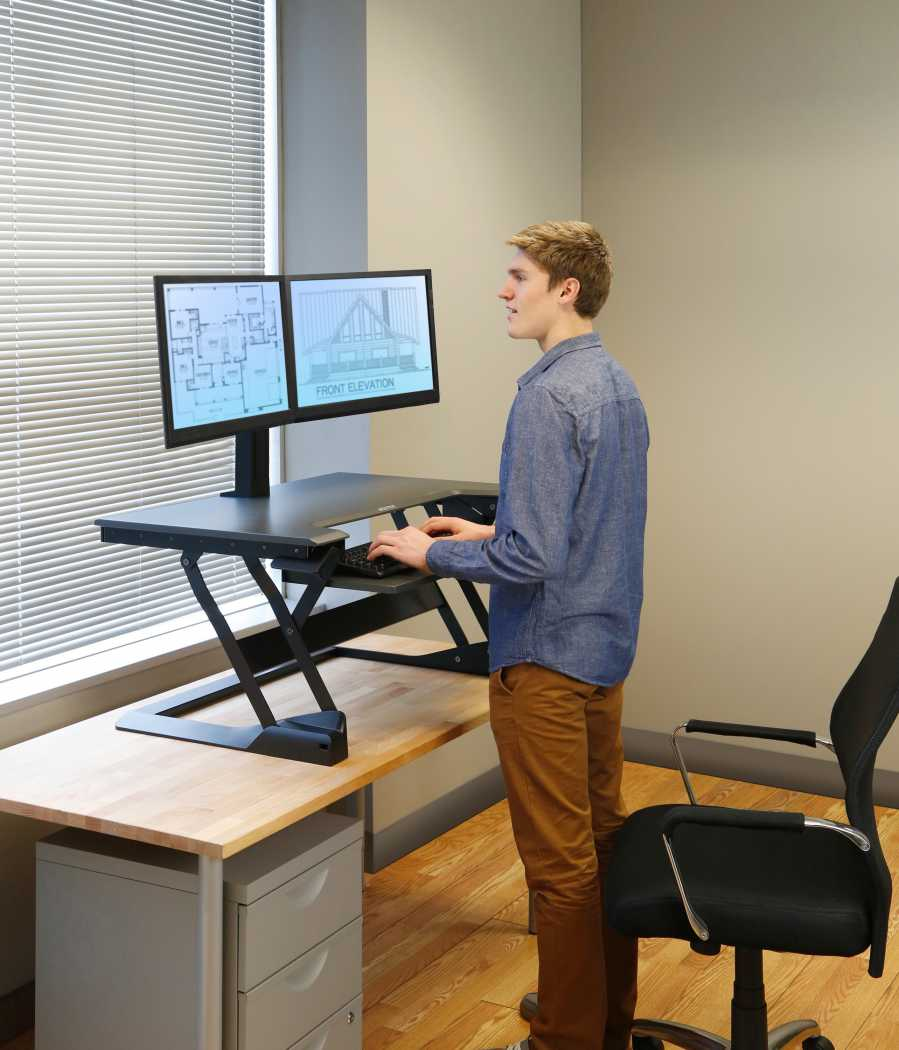 A man is using a sit stand workstation